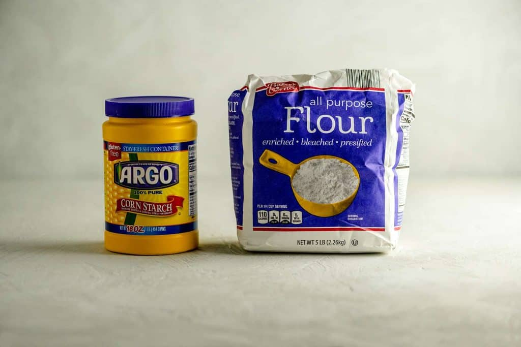 Yellow container of cornstarch next to a 5 lb bag of flour on a gray table