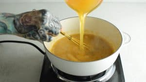 pouring ham broth into butter and flour mixture in skillet