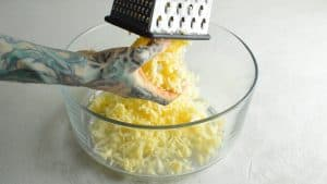 White cheddar coming out of a cheese grater into a clear glass bowl