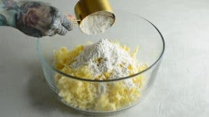 Flour being pour onto grated cheddar