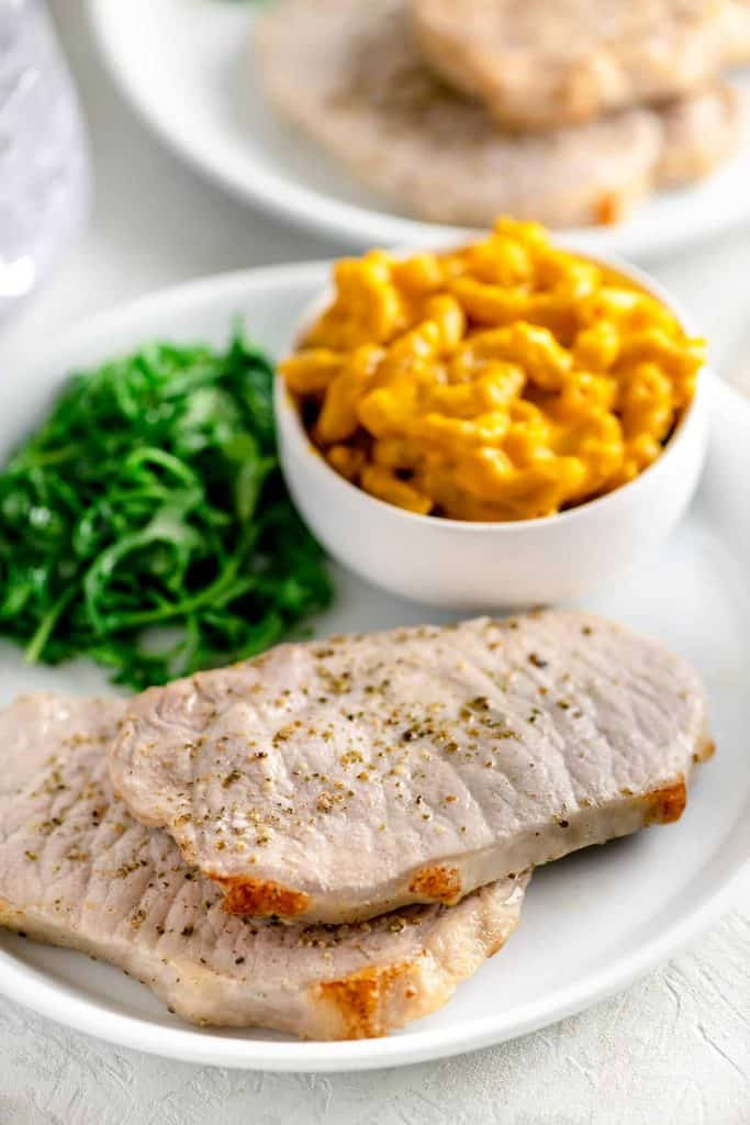 White plate with two pork chops beside mac and cheese and arugula