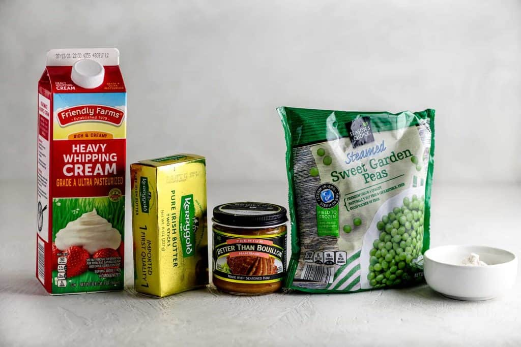 Container of cream next to kerrygold butter, ham better than bouillon, bag of frozen peas and flour on a gray table