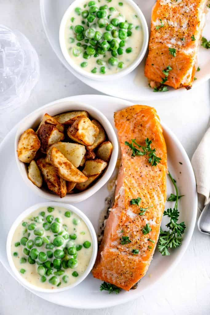 cup of creamed peas beside a cup of roasted potatoes and fillet of salmon