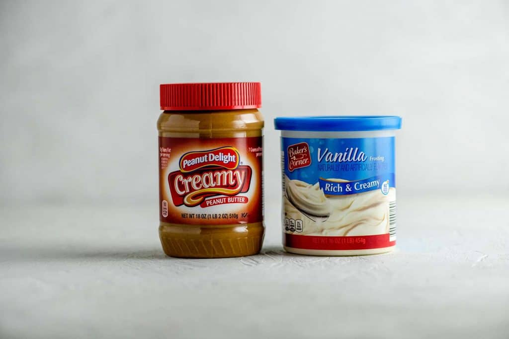 Jar of peanut butter and container of vanilla frosting on a gray table