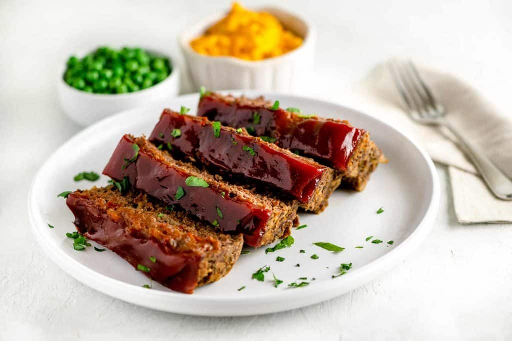 Thick cut of meatloaf with a rich ketchup glaze on a white plate beside a bowl of macaroni and cheese and green peas.