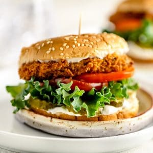 Vegan Fried Chicken sandwich on a plate with lots of lettuce, tomato and pickles