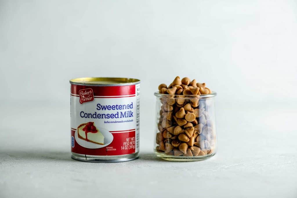 Can of sweetened condensed will next to a glass jar of peanut butter chips