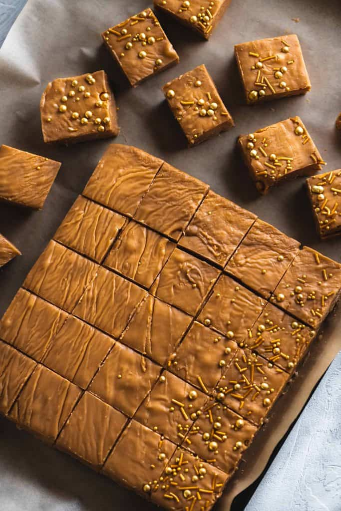 Large tray of peanut butter fudge but into squares and topped with shiny sprinkles